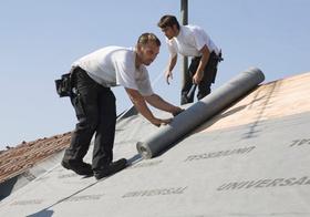 2 Männer decken Dach ein