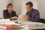 2 Männer im Büro lesen Unterlagen