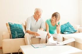 2 Senioren auf der Couch schauen sich Papiere an