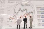 Drei Businessmann Figürchen schauen durch eine Lupe auf eine Börsenchart/ein Diagramm