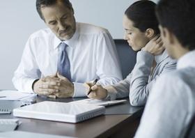 3 Personen arbeiten an Konferenztisch