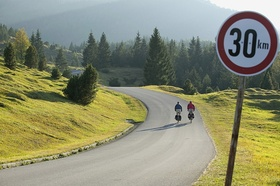 30 km Schild vor grüner Landschaft und kleiner Straße mit Fahrradfahrern