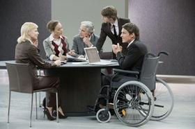 Rollstuhlfahrer am Meetingtisch mit Kollegen und Laptop