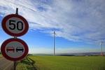 50 und Überholen verboten Schild mit grüner Landschaft und Windrädern im Hintergrund