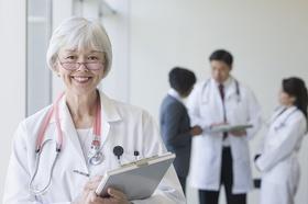 Ältere Ärztin mit anderen Ärzten im Hintergrund