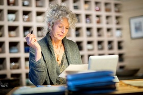 ältere Dame arbeitet an Schreibtisch im Büro
