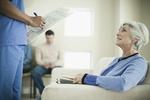 Ältere Dame im Wartezimmer die mit Pfleger spricht