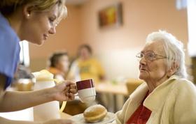 Ältere Frau bekommt Getränk und Essen von Pflegepersonal