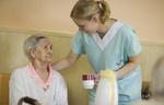 Ältere Frau bekommt Getränk von Pflegeperson