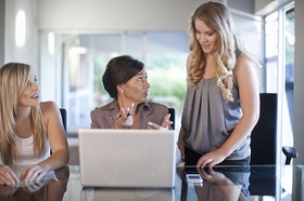 Ältere Frau erklärt jungem Mädchen etwas am Laptop