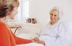 Ältere Frau im Bett hält Hand von Pflegeperson