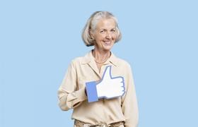 Ältere Frau mit Facebook Daumen