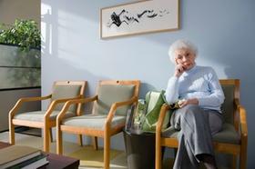 Ältere Frau sitzt u wartet, 3 Stühle im Wartezimmer