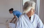 Ältere Frau und Pflegeperson beim Bettenmachen