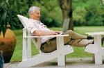 Älterer Herr mit Laptop im Garten