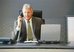 Älterer Manager sitzt am Schreibtisch, telefoniert
