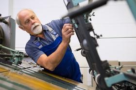 Älterer Mann an Maschine in der Produktion
