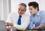 Älterer Mann erklärt Jugendlichem etwas am Laptop