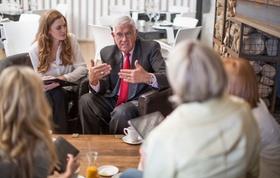 Älterer Mann gestikuliert und unterhält sich mit Menschen