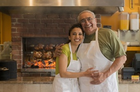Älterer Mann hat jüngere Frau im Arm Hintergrund Restaurant Ofen