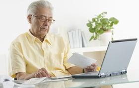 Älterer Mann mit Rechnungen vor Laptop