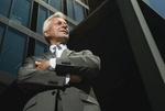 Älterer Mann verschränkt Arme vor Glas-Hochhaus-Fassade