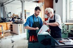 Älterer und jüngerer Mann Arbeiten zusammen an Druckmaschine