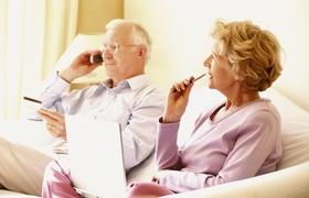 Älteres Ehepaar auf Sofa telefonierend und Notizen machend