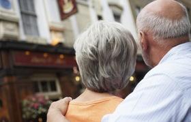 Älteres Ehepaar von Hinten mit Blick auf Gebäude