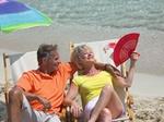 Aelteres Paar sitzt am Strand in Liegestuehlen