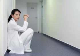 Ärztin hockt an einer Wand im Flur