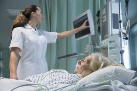 Pflegerin Ärztin schaut auf Bildschirm im Vordergrund alte Frau in Krankenbett