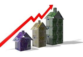 Aktienkurve mit Häusern aus Geld