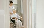 Alte Frau im Rollstuhl betreut von Pflegepersonal