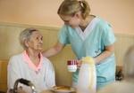Altenheim, Pflegerin bringt Seniorin eine Tasse