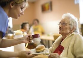 Altenheim, Pflegerin gibt Seniorin eine Tasse und Gebaeck
