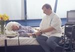 Altenpfleger beim Blutdruckmessen bei aelterer Seniorin am Bett