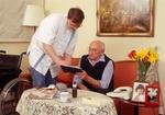 Altenpfleger zeigt aelterem Senior Unterlagen