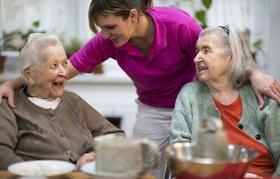 Altenpflegerin unterhält sich mit zwei älteren Frauen