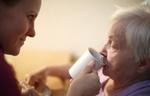 Altenpflegerin unterstützt ältere Frau beim Trinken
