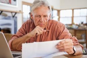 Alter Mann am Laptop der sich etwas durchliest