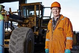 Alter Mann mit Bagger auf Baustelle