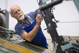 Alter Mann untersucht ein Maschinenteil