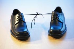 An den Schnürsenkeln zusammengebundene Schuhe