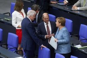 Angela Merkel, Olaf Scholz und Horst Seehofer unterhalten sich im Bundestag
