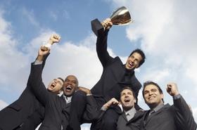 Anzugträger feiern mit Pokal unter blauem Himmel