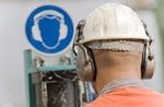 Arbeiter mit Schutzhelm vor Sicherheitshinweis