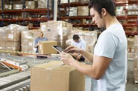 Arbeiter scannt Paket auf dem Fließband