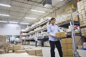 Arbeiterin kontrolliert Paket in Lagerhalle-Regale voller Pakete im Hintergrund