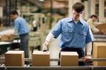 Arbeitnehmer steht an Fließband und scannt Pakete